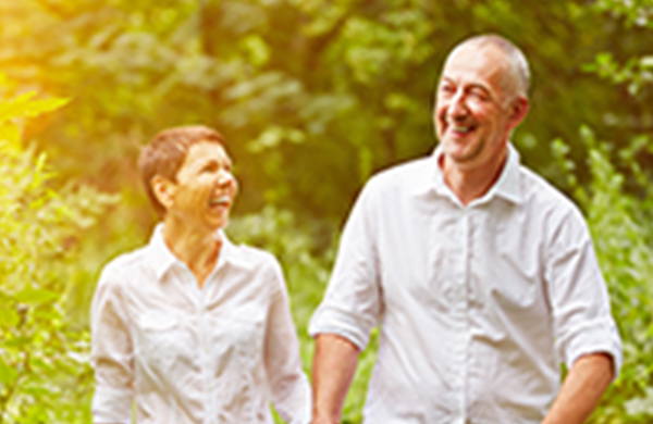 Hombre y mujer de mediana edad caminando por un campo, sonrientes y de la mano