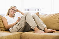 Woman resting on couch listening to music with headphones