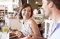 Young woman and man laughing while eating in a deli